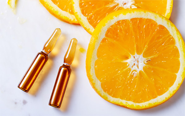 Vitamina C en ampollas y rodajas de naranja